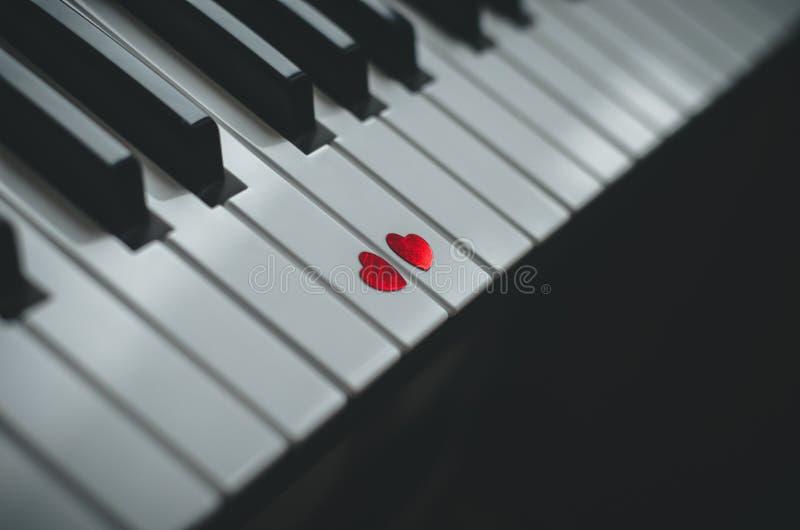 Dos pequeños corazones rojos en el teclado del cierre clásico del piano para arriba Concepto de amor y de música romántica fotografía de archivo