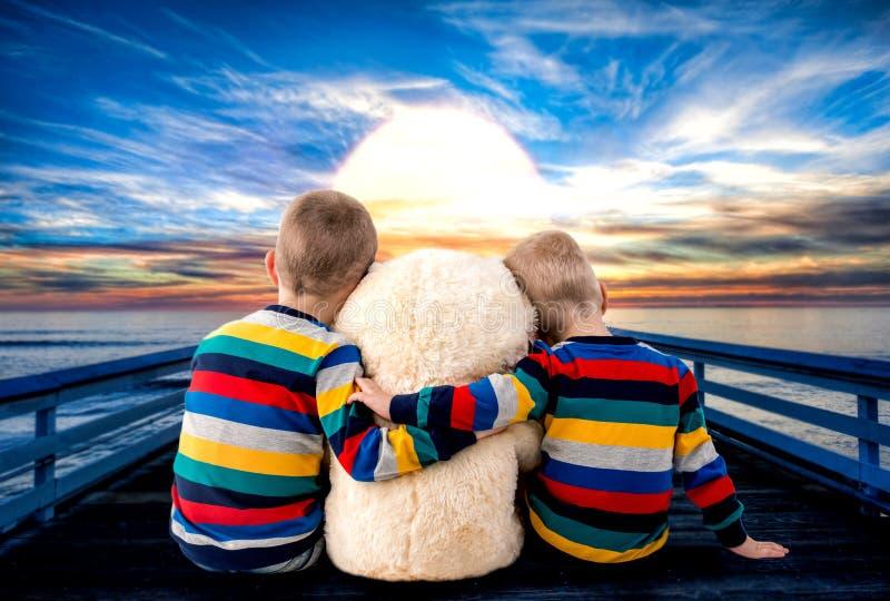 Dos pequeños hermanos con el oso que mira la puesta del sol fotografía de archivo libre de regalías