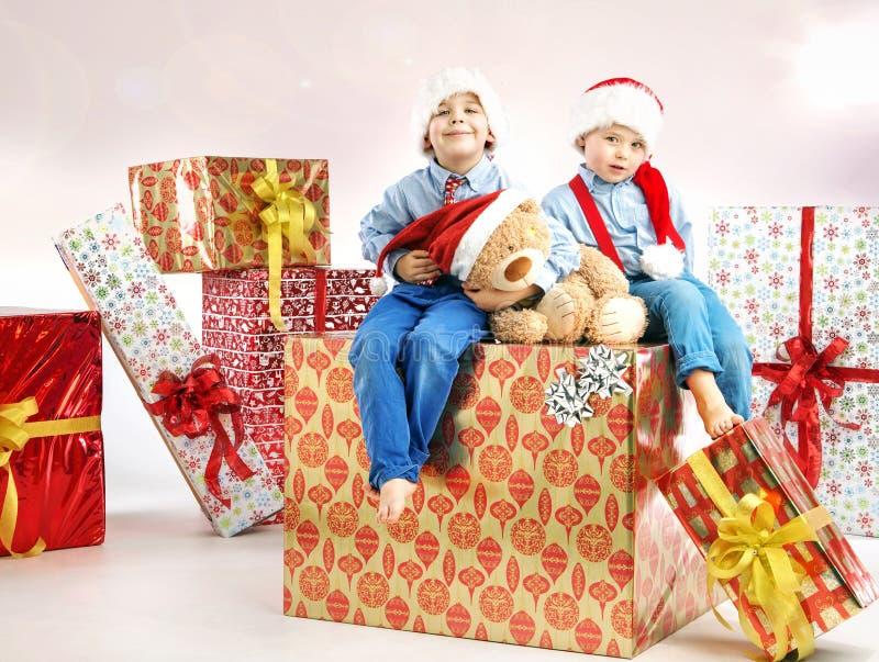 Dos pequeños hermanos entre presentes foto de archivo libre de regalías