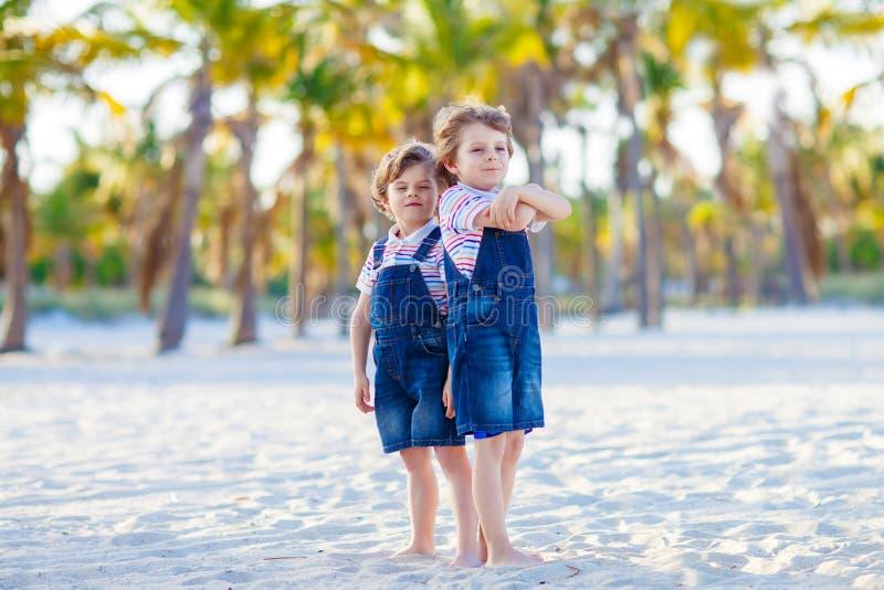 Dos pequeños hermanos preciosos que se sientan en la arena en la playa tropical, mejores amigos felices, embroman a los muchachos fotografía de archivo