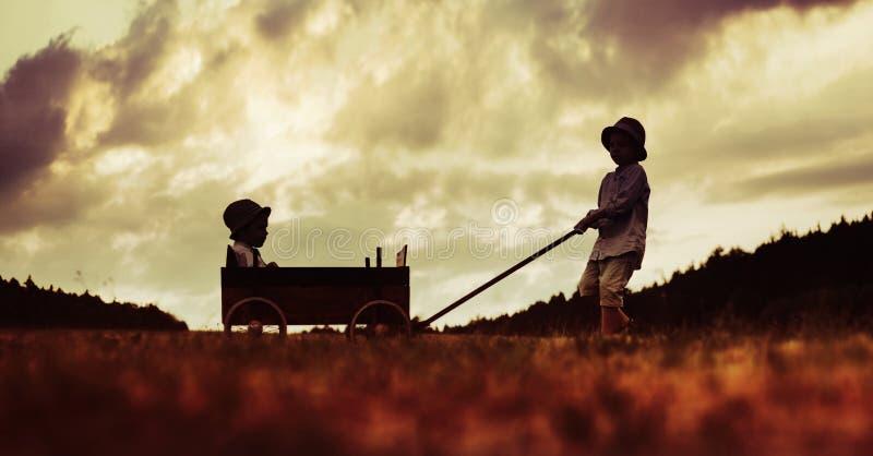 Dos pequeños hermanos que juegan con el carro de madera fotos de archivo