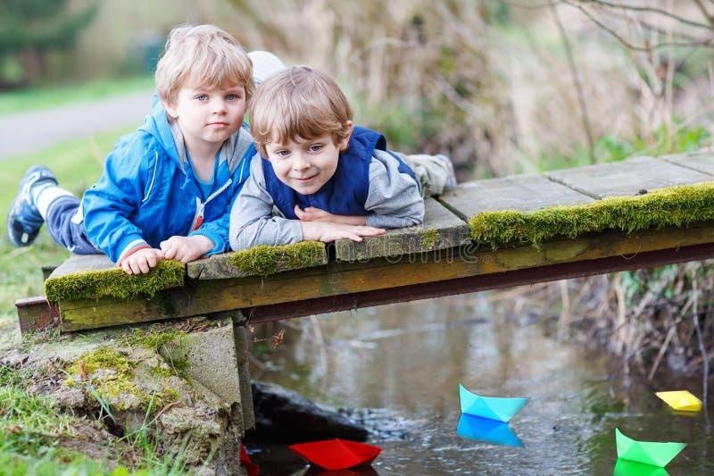 Dos pequeños hermanos que juegan con los barcos de papel por un río imagen de archivo