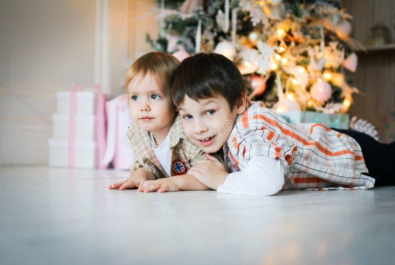 Dos pequeños hermanos que mienten en el piso cerca de un árbol de navidad imagenes de archivo