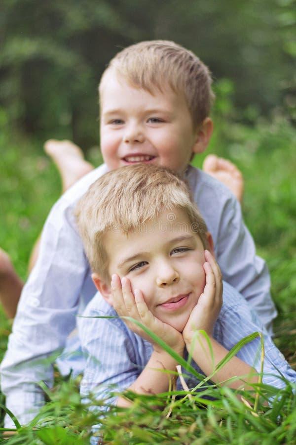 Dos pequeños hermanos que se relajan en una hierba imágenes de archivo libres de regalías