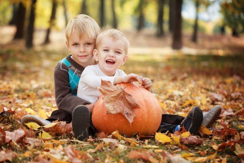 Dos pequeños hermanos que se sientan en hierba y que abrazan con la calabaza enorme en día del otoño foto de archivo