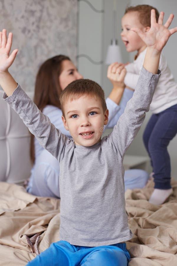 Dos pequeños hermanos se divierten con su madre joven vestida en pijama azul claro en la cama con la manta beige en imagen de archivo libre de regalías
