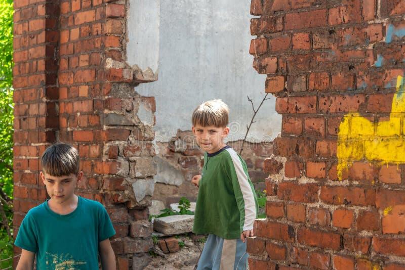 Dos pequeños hermanos son huérfanos, viviendo en una casa abandonada y abandonada, los niños de la guerra Foto efectuada fotografía de archivo libre de regalías