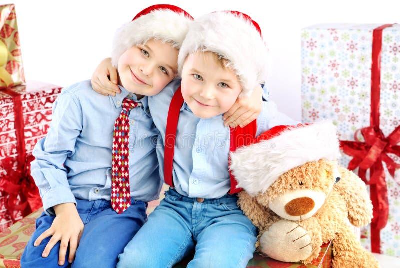 Dos pequeños hermanos sonrientes entre presentes imagen de archivo