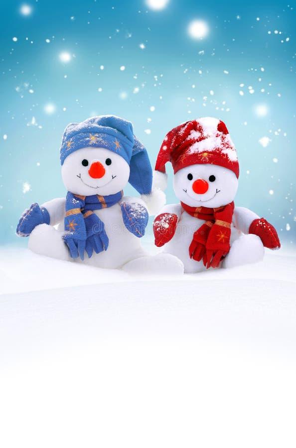 Dos pequeños muñecos de nieve la muchacha y el muchacho en casquillos y bufandas en nieve en el invierno Fondo con un muñeco de n imagen de archivo libre de regalías