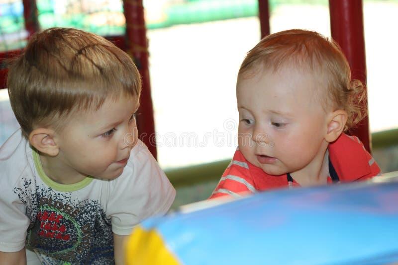 Dos pequeños muchachos divertidos del niño en parque de atracciones Amigos felices que se divierten al aire libre el día soleado imagen de archivo