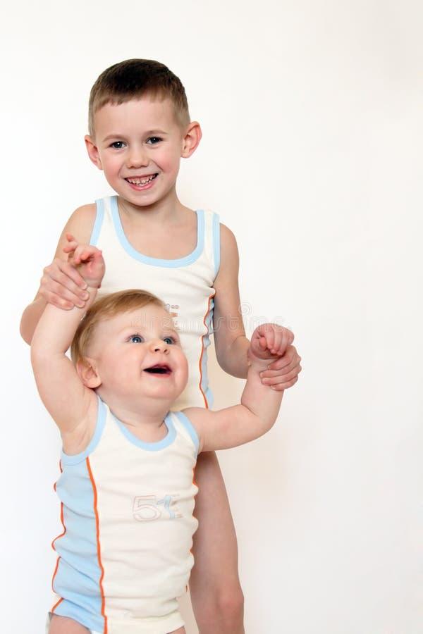 Dos pequeños muchachos en ropa idéntica imagen de archivo libre de regalías