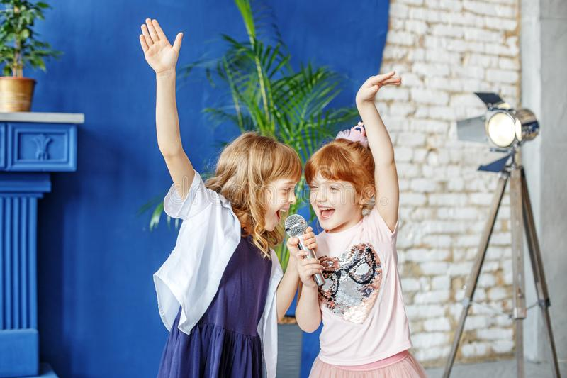 Dos pequeños niños divertidos bailan y cantan una canción en Karaoke E imagenes de archivo