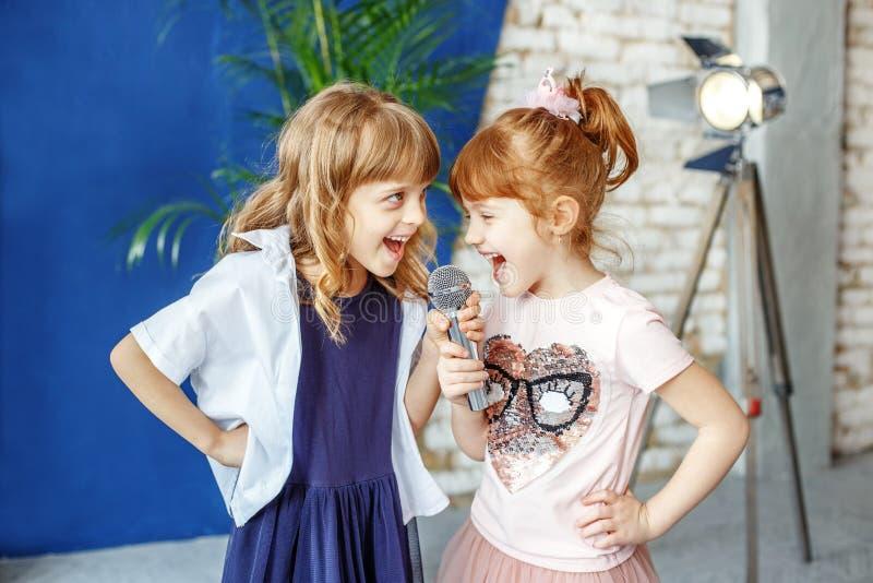 Dos pequeños niños felices cantan una canción en Karaoke El concepto es foto de archivo