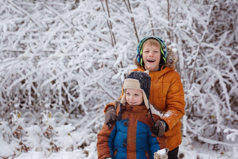 Dos pequeños niños, hermanos del muchacho que juegan al aire libre durante las nevadas Ocio activo con los niños en invierno en d imagenes de archivo