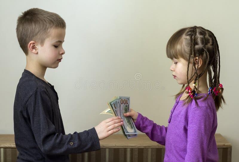 Dos pequeños niños muchacho y muchacha que juegan con el dinero de los dólares foto de archivo libre de regalías