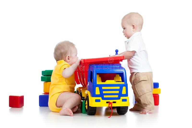 Dos pequeños niños que juegan con los juguetes del color fotografía de archivo
