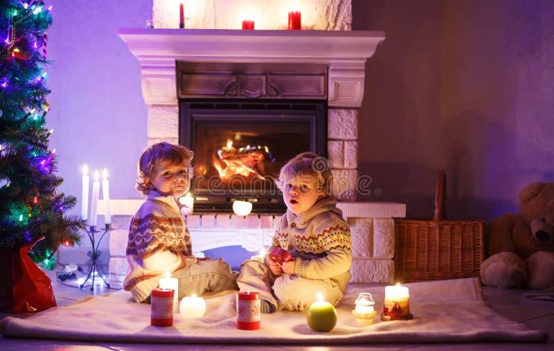Dos peque os ni os que se sientan por una chimenea en casa for Chimeneas en apartamentos pequenos