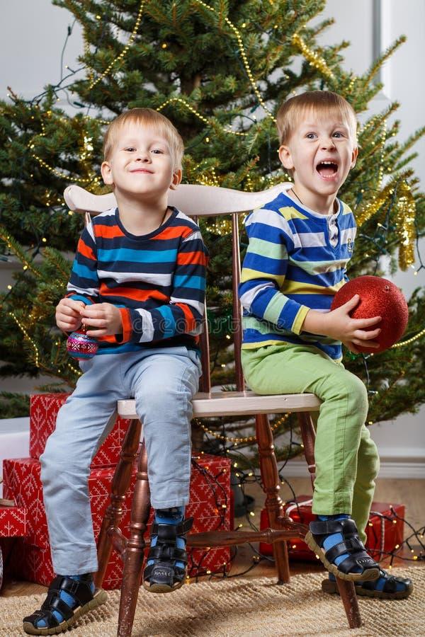 Dos pequeños niños sonrientes, muchachos guardan bolas en fondo del árbol de navidad Niños amistosos felices Foco selectivo fotos de archivo libres de regalías