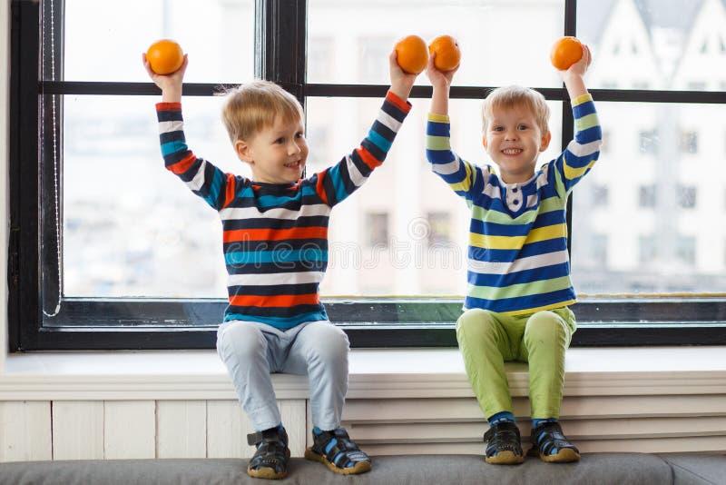 Dos pequeños niños sonrientes, muchachos guardan la sentada anaranjada de las frutas en el alféizar Niños amistosos felices foto de archivo