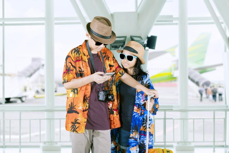 Dos pequeños turistas que usan un teléfono en el aeropuerto fotografía de archivo