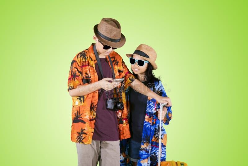 Dos pequeños viajeros que usan un teléfono en el estudio foto de archivo libre de regalías