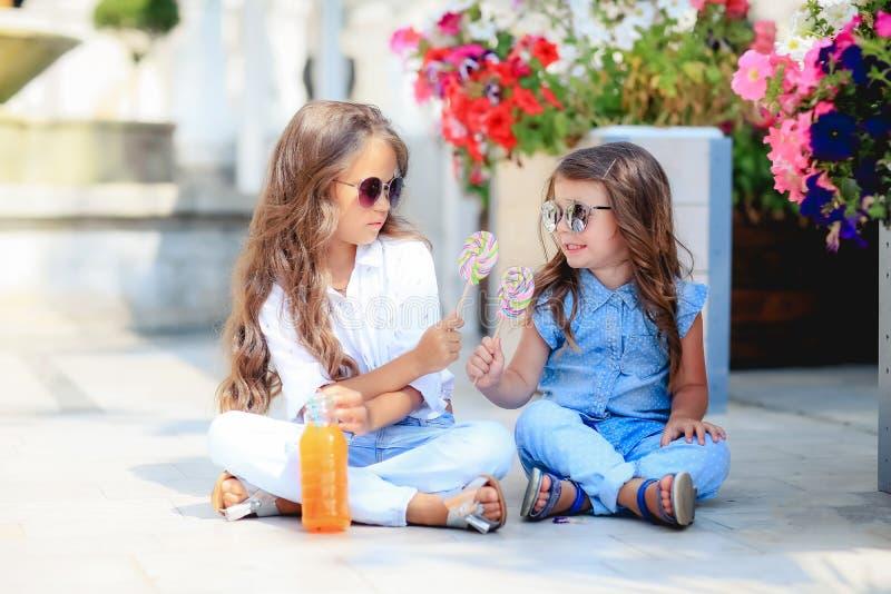 Dos peque?as hermanas lindas que comen las piruletas enormes al aire libre en d?a de verano hermoso fotografía de archivo