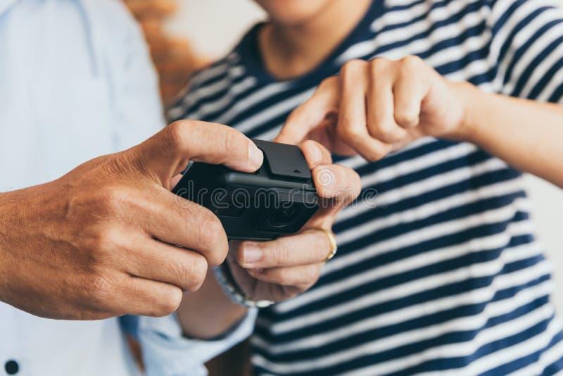 Dos personas de los hombres que fijan el vídeo de la cámara de la acción mientras que se sostiene para la mejor grabación de la l imágenes de archivo libres de regalías