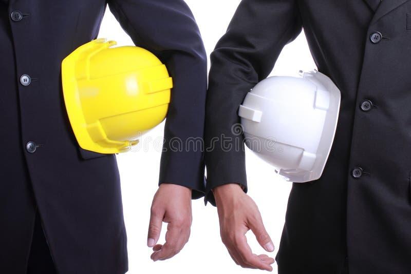 Dos personas del ingeniero que sostienen el sombrero de seguridad imagenes de archivo