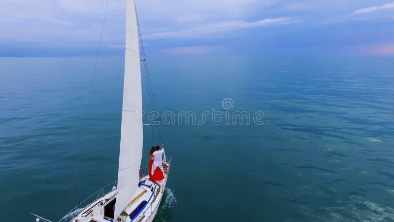 Dos personas en el amor que se coloca en el arco de la navegación del barco hacia horizonte, recienes casados imagen de archivo