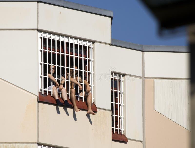 Dos personas en la prisión detrás del cedazo fotografía de archivo libre de regalías
