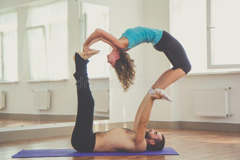 Dos personas están haciendo acro-yoga dentro imagen de archivo