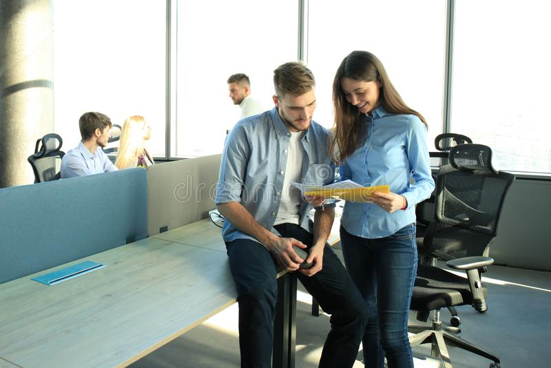 Dos personas jovenes felices en ropa de sport que sonríen y que miran la tableta digital mientras que trabaja junto imagen de archivo