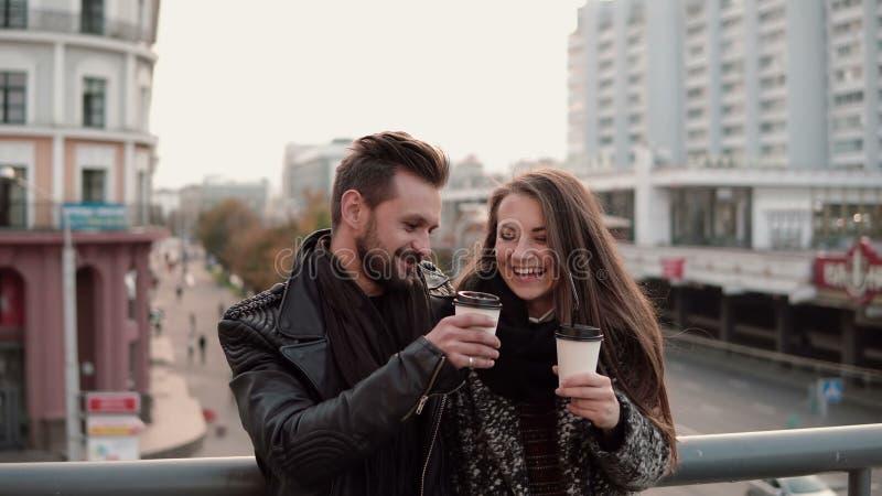 Dos personas jovenes felices se divierten El hombre joven hermoso y la muchacha hermosa ríen alegre, sosteniendo el café para lle fotografía de archivo libre de regalías
