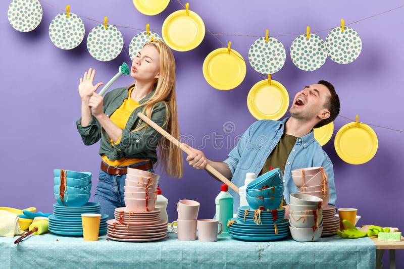 Dos personas jovenes que disfrutan del canto en la cocina imagen de archivo