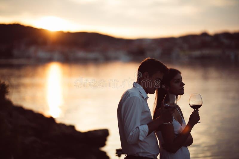 Dos personas jovenes que gozan de un vidrio de vino rojo en la puesta del sol en la playa Vino rojo hecho en casa del od del vidr foto de archivo