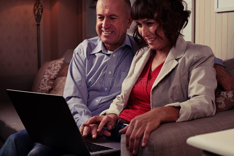 Dos personas mayores que se sientan en el sofá, sonriendo y mirando t fotografía de archivo libre de regalías