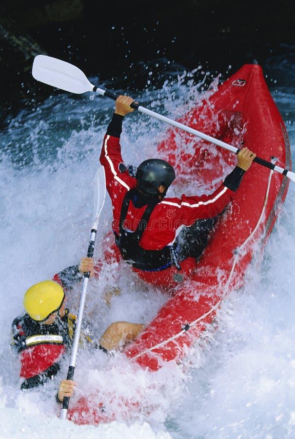 Dos personas que baten rapids inflables del barco abajo imágenes de archivo libres de regalías
