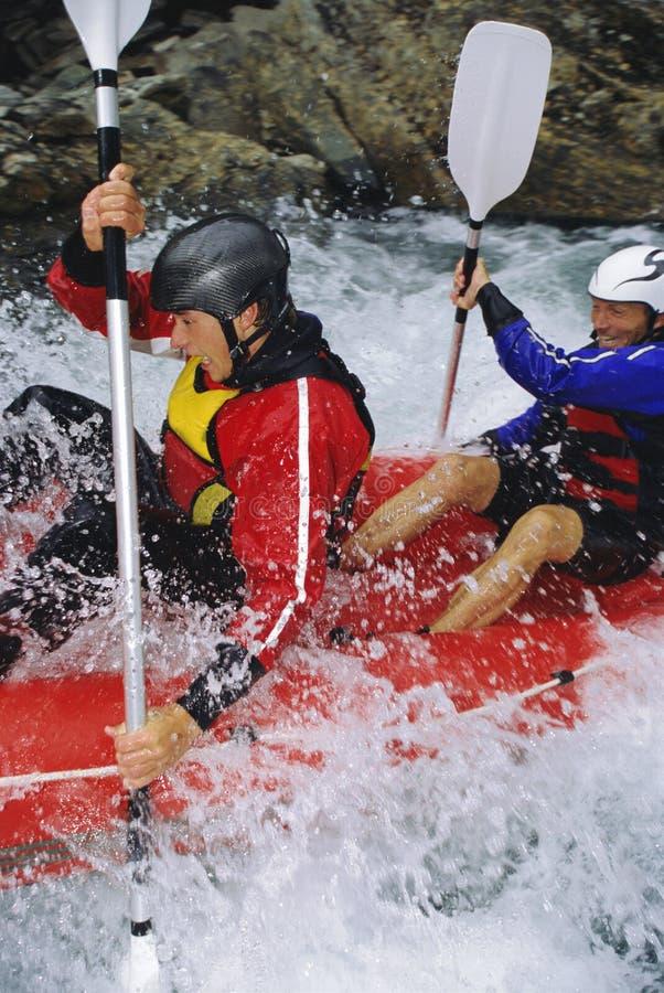 Dos personas que baten rapids inflables del barco abajo foto de archivo libre de regalías