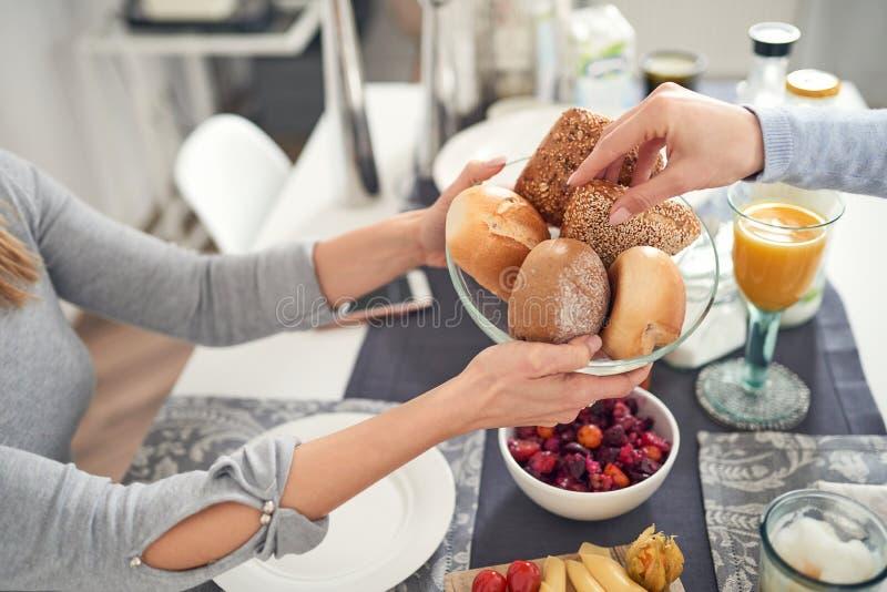 Dos personas que comen el desayuno que selecciona los rollos de pan imagenes de archivo