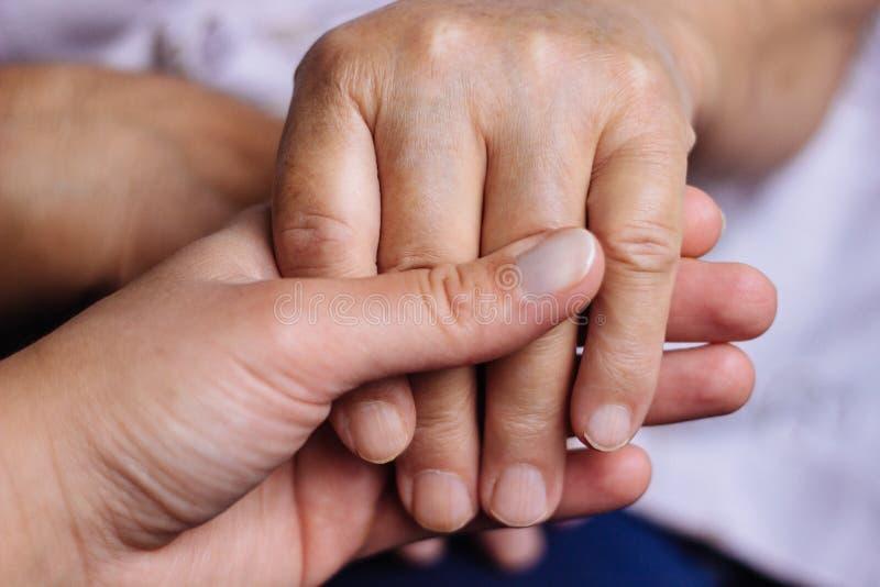 Dos personas que llevan a cabo las manos de cada uno imagen de archivo