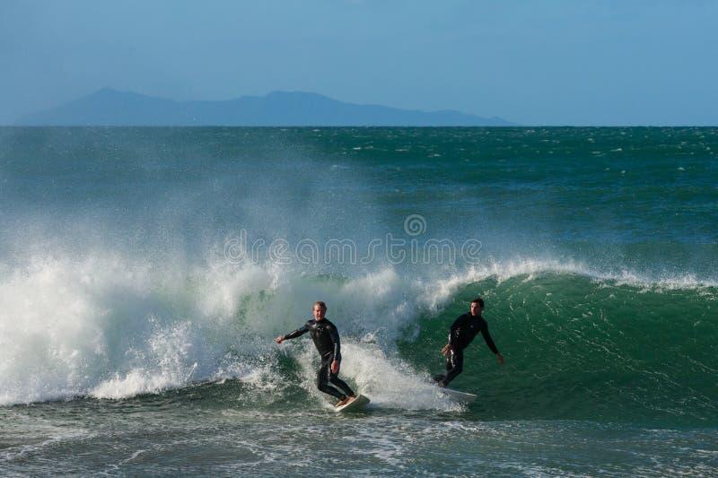 Dos personas que practica surf chocan casi mientras que cogen la misma onda imagenes de archivo