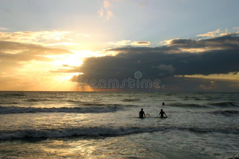 Dos personas que practica surf en la puesta del sol foto de archivo libre de regalías