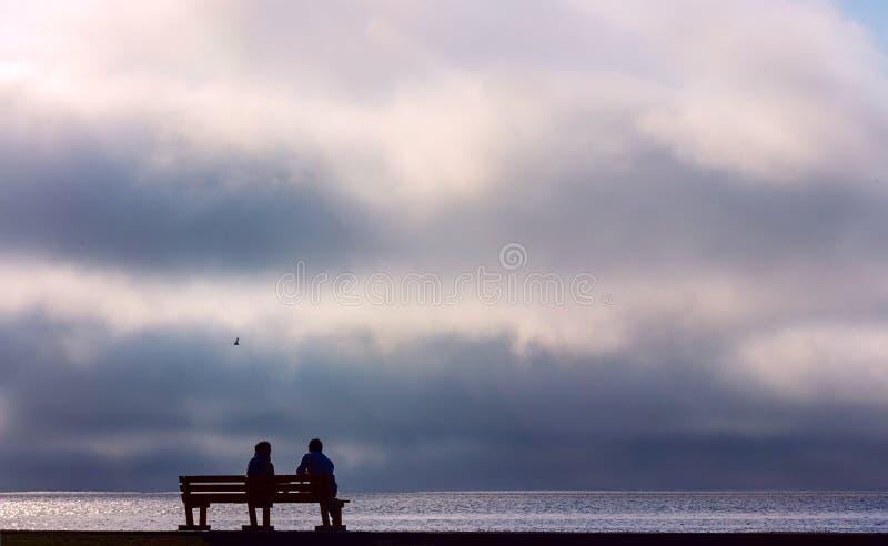 Dos personas que se sientan en un banco de la calle y que miran la puesta del sol dramática foto de archivo libre de regalías