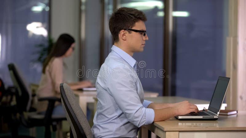 Dos personas que trabajan en el ordenador portátil en la oficina grande, soporte técnico, centro de servicio foto de archivo