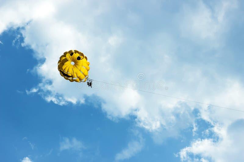 Dos personas se están deslizando usando un paracaídas en el fondo del cielo azul Fondo del verano imagenes de archivo