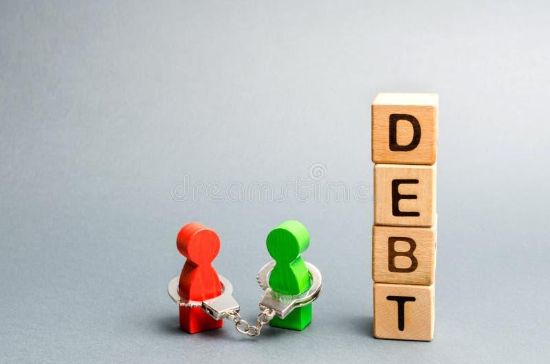 Dos personas son limitadas por las esposas con la deuda de la palabra Acreedor y deudor Esclavitud financiera Compromisos de Uncl imágenes de archivo libres de regalías