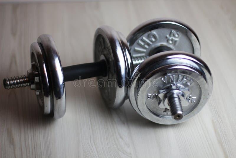 Dos pesas de gimnasia del hierro en un fondo de madera fotografía de archivo