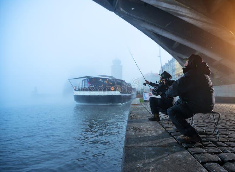 Dos pescadores que intentan coger pescados en el río, pesca urbana imagenes de archivo