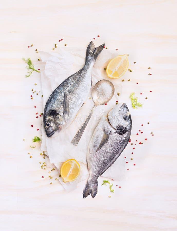 Dos pescados crudos del dorado con el limón, las especias y la cuchara en el papel, componiendo en el fondo de madera blanco, fotografía de archivo