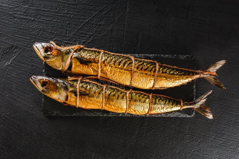 Dos pescados de la caballa ahumada en fondo de la piedra de la pizarra La comida mediterr?nea, arenque pesca, los mariscos, cierr imagen de archivo libre de regalías